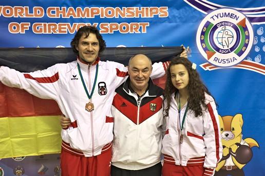 Karsten Bollert, Johann Martin und Josephine Pora vor der Stellwand der Kettlebell Weltmeisterschaft 2013 in Tjumen Russland.